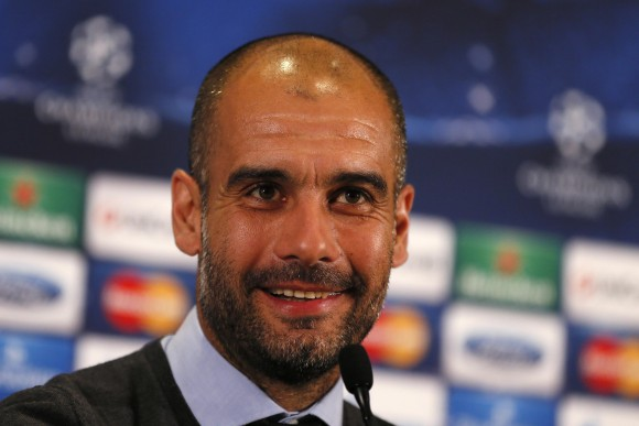 Bayern Munich's coach Guardiola smiles during a news conference at Old Trafford in Manchester